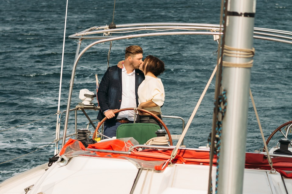 A couple on a yacht kissing.