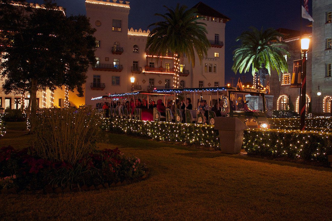 A photo of people riding the Old Town Trolley in front of the Lightner Museum during St. Augustine's Nights of Lights holiday display.
