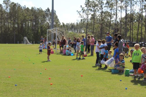Image contains outdoors, grass, trees, and children looking for Easter Eggs.