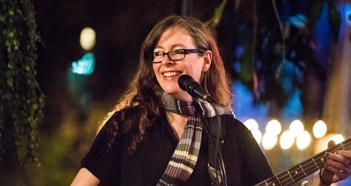 Image of Elizabeth Roth performing at Tradewinds; long brown hair, wearing dark glasses