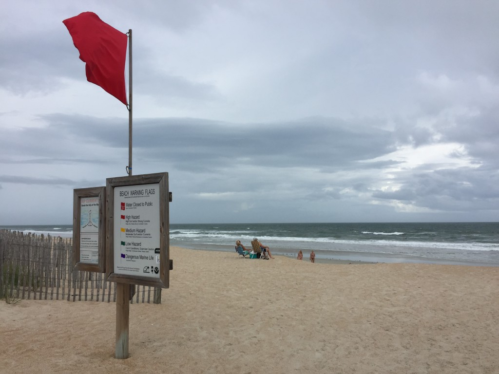 Image contains dark clouds rolling over a stormy sea and a beach warning flag.