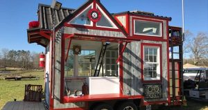 A wooden tiny house that is red and white.