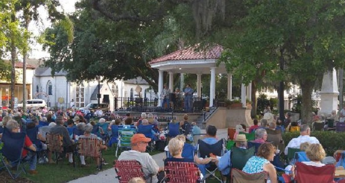 People sitting on the lawn or in chairs around the Gazebo listening to Concerts in the Plaza