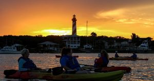 kayakers at sunset with St. Augustine Lighthouse in background