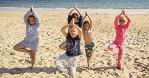 3 or 4 kids on the beach doing yoga