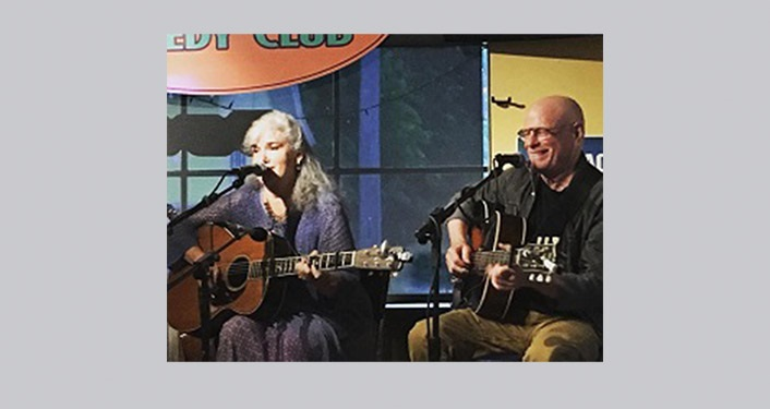 image of local musicians, Lis Williamson and Jim Quine, sitting, playing guitars and singing