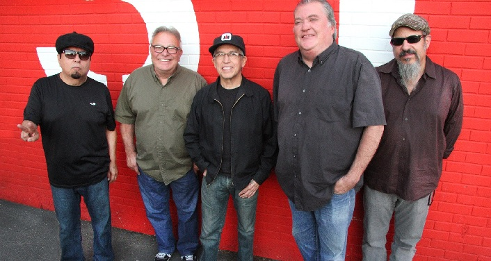 A band of five men, the Los Lobos, posing for a photo in front of a red wall.