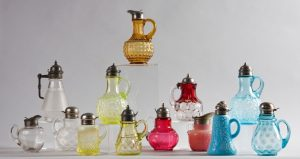Various sizes and colors of pressed glass syrup bottles; one of the special exhibits to be seen during the Lightner Museum Curator's Tour