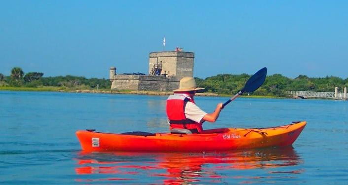 image of bright orange kayak with person wearing white shirt and life vest, paddling in front of Fort Matanzas on a Fort Matanzas Kayak Trip