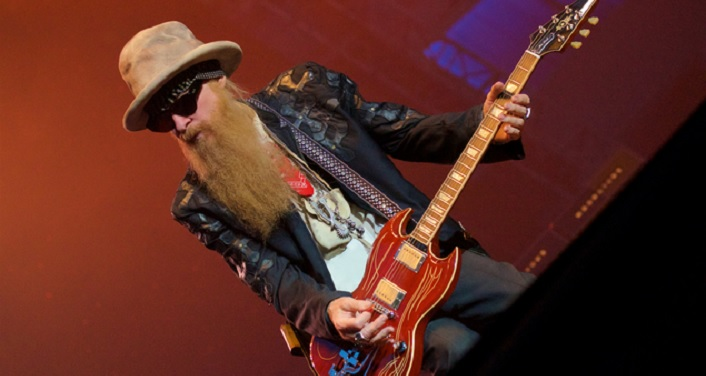 Billy Gibbons in a leather jacket, hat, and sunglasses playing a red electric guitar.