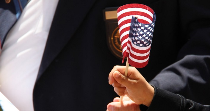 image of child's hand, in foreground, holding small American flag on stick; in background dark jacket with medals pinned to left side. Veteran's Day Memorial