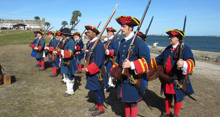 Men dressed in militia outfits from 1763-1784, standing in formation outside of the Castillo