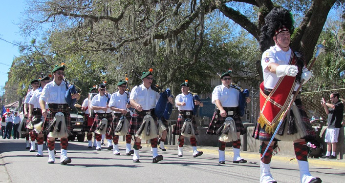 image of fife & drum corp, mean wearing kilts, tartans, white shirts, and green berets marching in St. Patrick's Day Parade