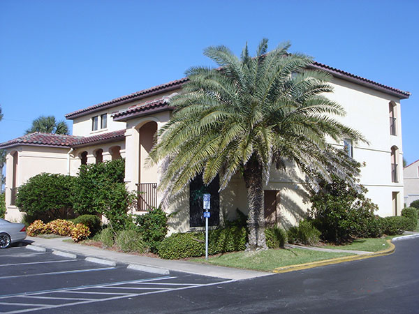 Image contains a handicap parking spot, a hotel, and palm trees.