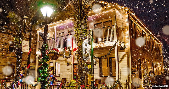 "niimage of ""snow"" falling in front of 44 Spanish Street Inn during Snowfall on Spanish Street. the Inn is decorated with Christmas wreaths and red bows and white lights."