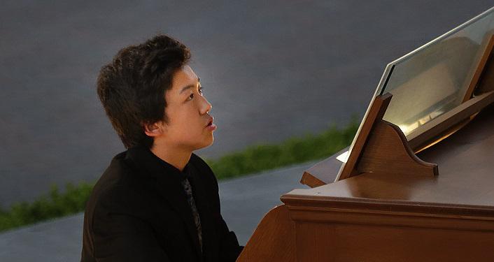 photo of young man, Bruce Xu, sitting at an organ performing
