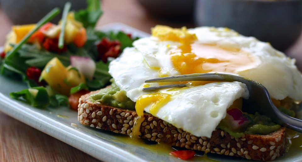 Image contains a fork cutting into an over easy egg on a piece of bread.