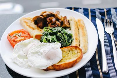 Image contains eggs, spinach, bacon, tomatoes, toast, and sausage on a plate.