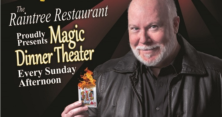 Bald Man holding a burning playing card with text Raintree Restaurant Magic Dinner Theatre