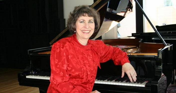 woman wearing red top sitting by a piano