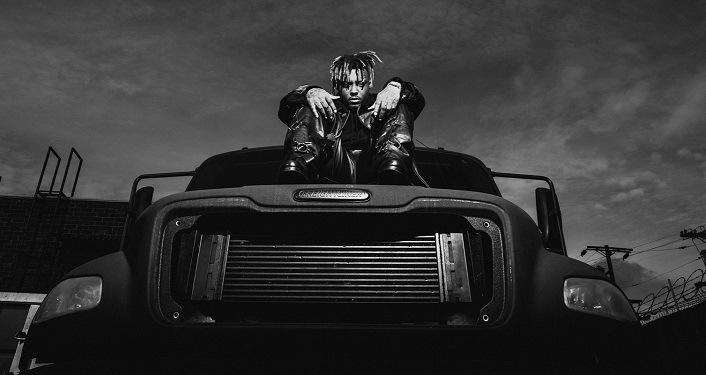 black and white image with Juice WRLD sitting on top of a car.