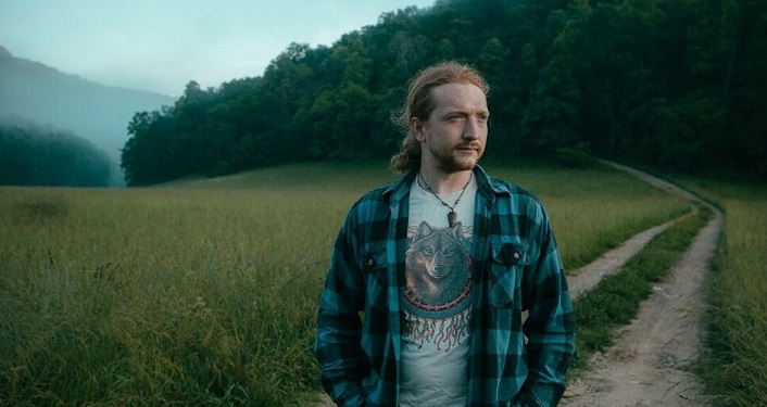 Tyler Childers stading gazing to his left, grassy meadow and trees in the background.