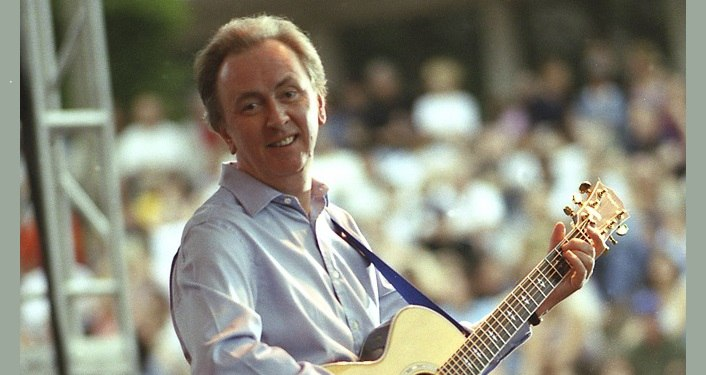 Image of Al Stewart playing guitar with audience in background.