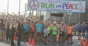 Runners, young & old, men & women, at the pier waiitng for start of the Betty Griffin Center Run For Peace 5K
