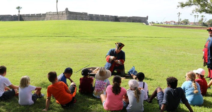 boys and girls sitting in grass outside of Castillo de San Marcos listening to re-enactor