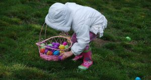 little girl putting Easter egg into basket with some Easter eggs.