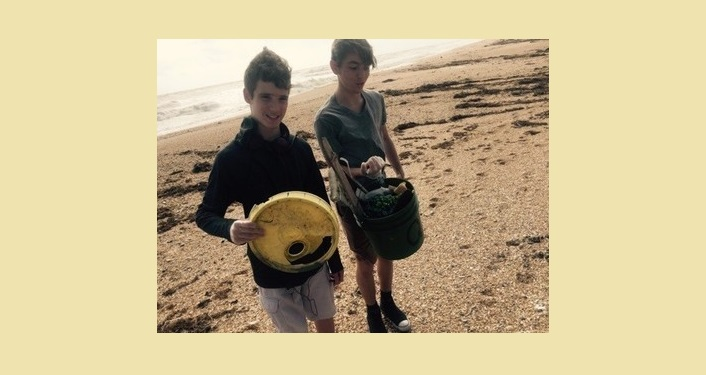 2 young boys on the beach holding trash they've picked up