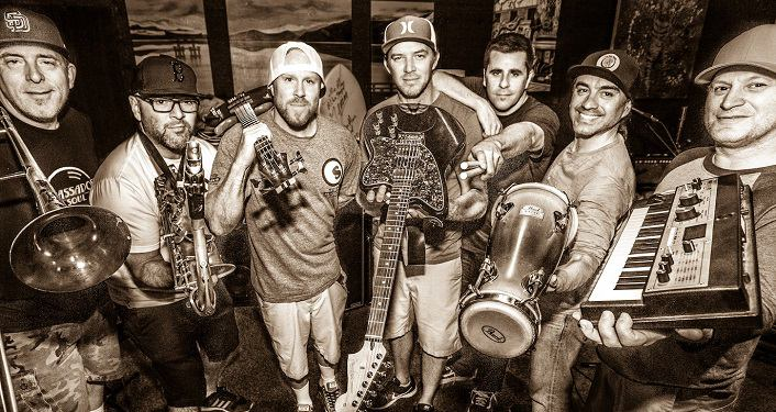 Black & whtie photo of the band Slightly Stoopid in semi-circle holding the instruments they play