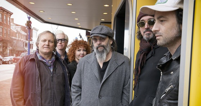 Image of Venerable roots rocker Steve Earle and his band, The Dukes, standing outside with jackets on.