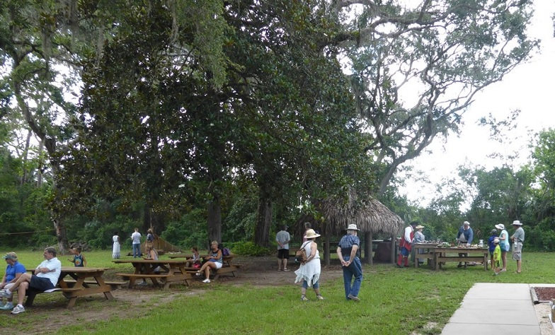 Image contains the outdoors, people walking, and picnic tables.