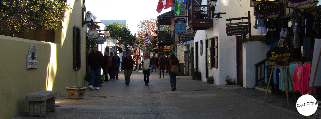Image contains people walking on a street lined with shops and boutiques.