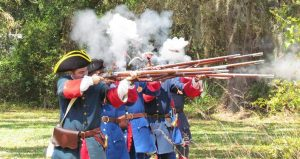 Reenactors dressed in 1700's garb, firing muskets during the Battle of Bloody Mose Reenactment