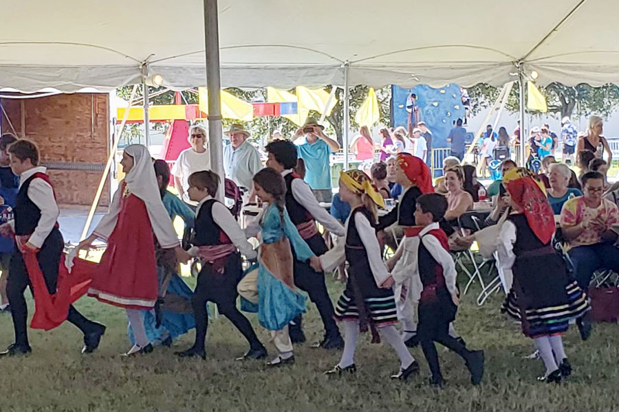 A group of children dancing in a line with people sitting in the background.