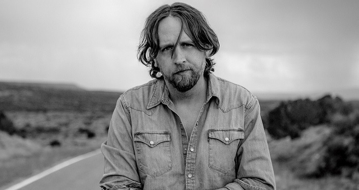 black & white image of Hayes Carll standing on empty road in New Mexico or Arizona