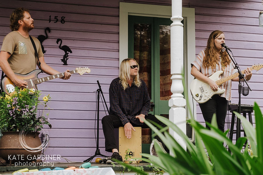 Two people playing the guitar and one person playing a drum on the front porch of a house.