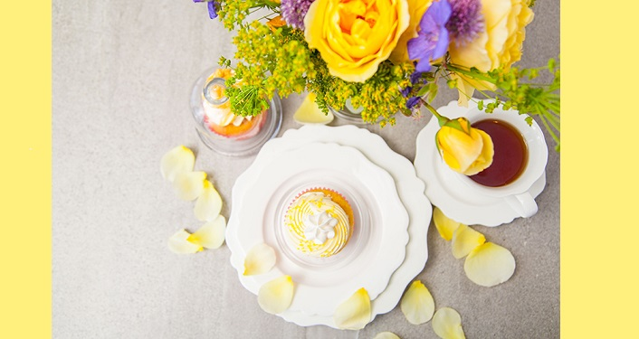 Cupcake on plate surrounded by flower petals, yellow rose in vase