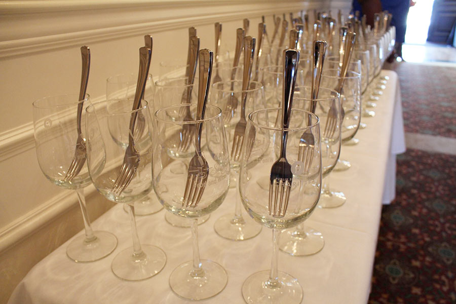 Four rows of wine glasses with a fork placed in them.