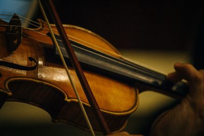 A closeup shot of a violin and a hand.