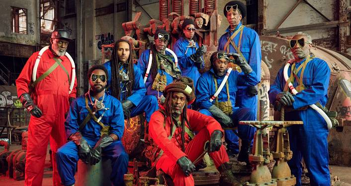 image of Roots reggae music pioneers Steel Pulse, two wearing red jumpsuits, seven wearing blue jumpsuits