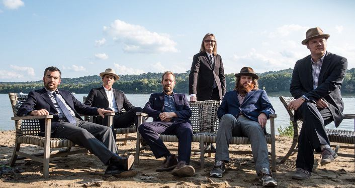 image of Steep Canyon Rangers with a lake in the background. Four of them are sitting, two are standing.
