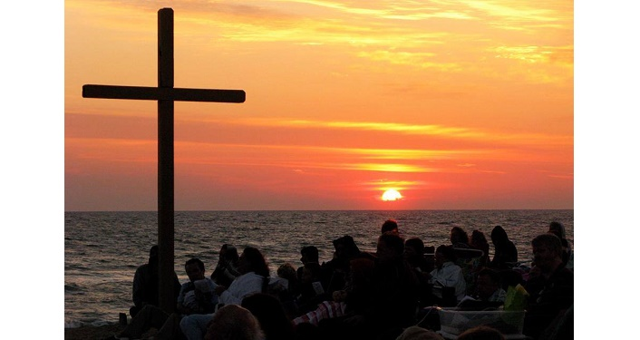 large cross and people on the beach watching sunrise on Easter Sunday