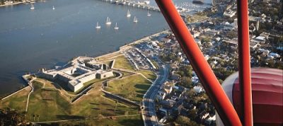 Image is an aerial view of the Castillo de San Marcos from a biplane. Image contains water, grass, and outdoors.
