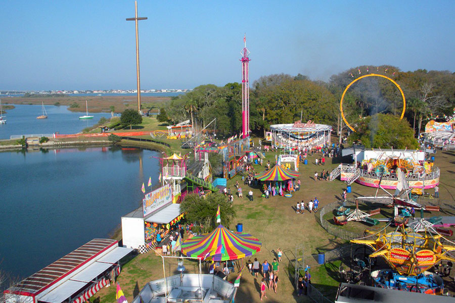 An aerial view of a large park that has theme park rides, people walk, and a giant cross.