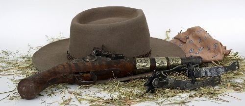 Image contains only the following props: cowboy hat, pistol, and hay.