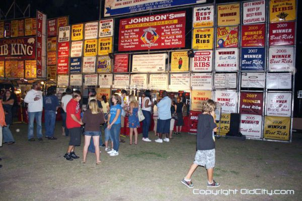 A group of people standing outside, in front of a tall fence with signs on it at Rhythm & Ribs Festival