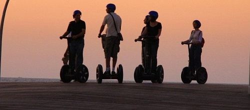 Image is of four people riding Segways on a boardwalk during sunset.
